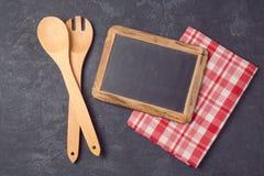 Fondo de la cocina con la pizarra, el mantel y los utensilios sobre piedra oscura Foto de archivo