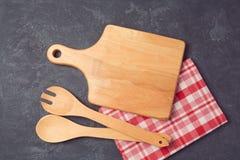Fondo de la cocina con la tabla de cortar, el mantel y los utensilios sobre piedra oscura Fotografía de archivo libre de regalías