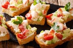 Fondo de la comida: bocadillos con la langosta, aguacate, tomates y fotografía de archivo