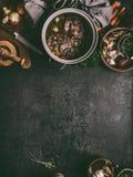 Fondo de la comida con la carne guisada de la carne de vaca en cocinar el pote en la tabla oscura con las hierbas, las especias y imagenes de archivo