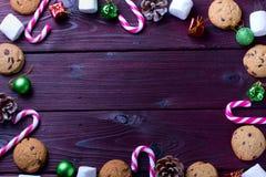 Fondo de la comida con el microprocesador de chocolate, las galletas, las melcochas y los bastones de caramelo foto de archivo