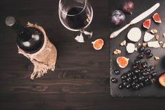 Fondo de la comida con el vino rojo, los higos, las uvas y el queso Foto de archivo libre de regalías