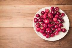 Fondo de la comida con las cerezas frescas en la tabla de madera con efecto retro del filtro Visión desde arriba Imagen de archivo libre de regalías
