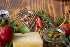 Fondo de la comida en la tabla de madera Queso del primer, pimientas, aceitunas verdes, tomates y especias para cocinar la comida foto de archivo