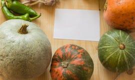 Fondo de la cosecha o de la acción de gracias con las frutas y las calabazas del otoño en una tabla de madera rústica, espacio de Imagenes de archivo