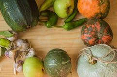 Fondo de la cosecha o de la acción de gracias con las frutas y las calabazas del otoño en una tabla de madera rústica Imágenes de archivo libres de regalías