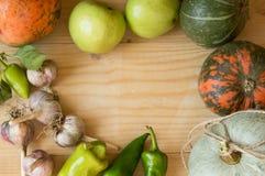 Fondo de la cosecha o de la acción de gracias con las frutas y las calabazas del otoño en una tabla de madera rústica Fotos de archivo