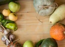 Fondo de la cosecha o de la acción de gracias con las frutas y las calabazas del otoño en una tabla de madera rústica Foto de archivo libre de regalías