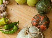 Fondo de la cosecha o de la acción de gracias con las frutas y las calabazas del otoño en una tabla de madera rústica, espacio de Foto de archivo