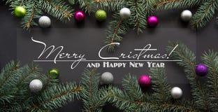 Fondo de la decoración de la Navidad o del Año Nuevo: el abeto ramifica, las bolas de cristal coloridas en negro Fotos de archivo
