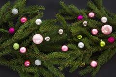 Fondo de la decoración de la Navidad o del Año Nuevo: el abeto ramifica, las bolas de cristal coloridas en fondo negro con el esp Imagenes de archivo