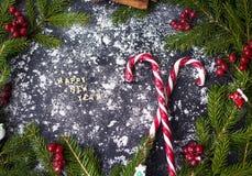 Fondo de la decoración de la Navidad o del Año Nuevo Para las ramas de árbol, caramelo en fondo negro Imagen de archivo libre de regalías