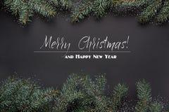 Fondo de la decoración de la Navidad o del Año Nuevo Ramas de árbol de abeto en fondo negro Visión superior Nieve exhausta Imagen de archivo libre de regalías