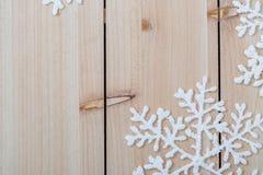 Fondo de la decoraci?n de la Navidad y espacio de la copia Copos de nieve artificiales blancos en una tabla de madera Feliz Navid imágenes de archivo libres de regalías