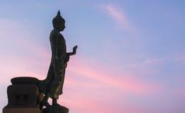 Fondo de la estatua de Buda en el soporte de la paz en el cielo hermoso del color crepuscular de la puesta del sol en el phuttham Imagen de archivo