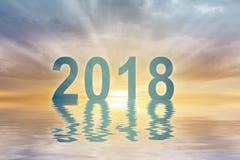 Fondo de la falta de definición de la puesta del sol del texto de los dígitos del Año Nuevo 2018 foto de archivo