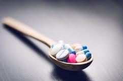 Fondo de la farmacia en una tabla negra con la cinta métrica Tabletas en una cuchara de madera Píldoras Medicina y sano Ciérrese  Foto de archivo
