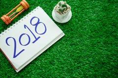 Fondo de la Feliz Año Nuevo con el reloj de arena, las plantas y el cuaderno ha Imagenes de archivo