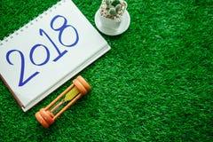 Fondo de la Feliz Año Nuevo con el reloj de arena, las plantas y el cuaderno ha Imagen de archivo libre de regalías