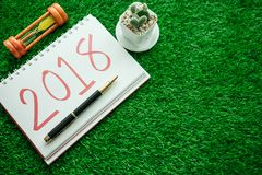 Fondo de la Feliz Año Nuevo con el reloj de arena, las plantas y el cuaderno ha Foto de archivo