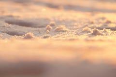 Fondo de la foto, nieve macra en luz de la puesta del sol De oro borroso y Imágenes de archivo libres de regalías