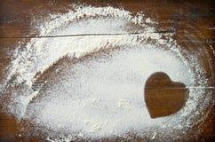 Fondo de la hornada con forma del corazón de la harina en el tabl de madera imagenes de archivo