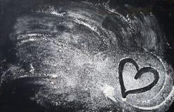 Fondo de la hornada con forma del corazón y harina en la tabla oscura fotos de archivo