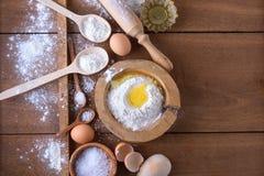 Fondo de la hornada con la harina, los huevos y los utensilios de la cocina Fotos de archivo