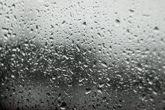 Fondo de la imagen de falta de definición del descenso del agua en fondo de la ventanilla del coche y de la calle Foto de archivo