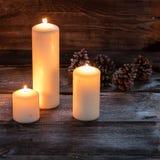Fondo de la luz de una vela del invierno con las velas grandes que brillan intensamente en la madera rústica Fotos de archivo