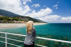 Fondo de la mujer rubia del mar, playa y montaña azules al aire libre, azules en Sicilia, Italia Fotografía de archivo