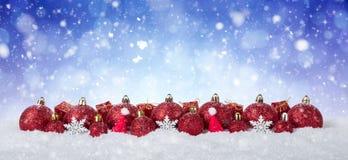 Fondo de la Navidad - bolas rojas adornadas en nieve con los copos de nieve y las estrellas Fotos de archivo libres de regalías