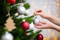 Fondo de la Navidad - cercano para arriba de la Navidad de adornamiento tr de la mujer Fotos de archivo