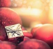 Fondo de la Navidad con bolas y un pequeño papier cadeau Fotos de archivo