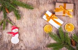 Fondo de la Navidad con el árbol de abeto, las cajas de regalo y el pan de jengibre Pan de jengibre en la forma del muñeco de nie Fotos de archivo