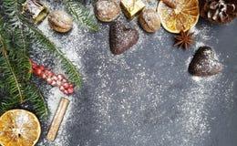 Fondo de la Navidad con el árbol de abeto de la nieve, las nueces y los panes de jengibre Foto de archivo