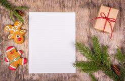 Fondo de la Navidad con el árbol de abeto, el regalo y el pan de jengibre Pan de jengibre pintado Hoja en blanco en un fondo de m Foto de archivo libre de regalías