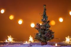 Fondo de la Navidad con el árbol de navidad, las velas, la nieve, los copos de nieve y las luces del bokeh Imagenes de archivo