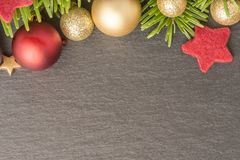 Fondo de la Navidad con el abeto, las chucherías y las estrellas en pizarra Imagenes de archivo