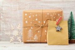 Fondo de la Navidad con el bolso hecho en casa del regalo, la caja y las decoraciones rústicas Foto de archivo libre de regalías