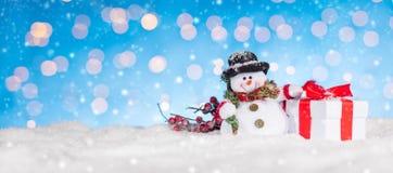 Fondo de la Navidad con el muñeco de nieve y los regalos Foto de archivo
