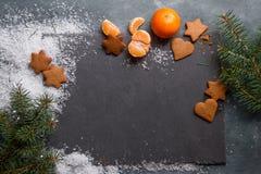 Fondo de la Navidad con el pan de jengibre, las galletas y las mandarinas Imagen de archivo libre de regalías
