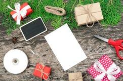 Fondo de la Navidad con el papel en blanco y pequeñas cajas de regalo y p Foto de archivo
