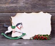Fondo de la Navidad con el papel vacío y el decoratio de madera del caballo Fotos de archivo