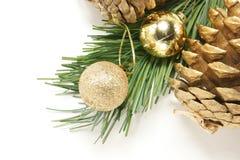 Fondo de la Navidad con el pino de oro de los conos y las pequeñas bolas Foto de archivo libre de regalías