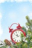 Fondo de la Navidad con el reloj y la rama Foto de archivo