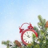 Fondo de la Navidad con el reloj y la rama Imagen de archivo libre de regalías