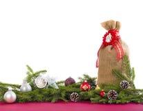 Fondo de la Navidad con el saco del yute, conos en blanco Foto de archivo
