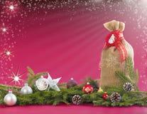 Fondo de la Navidad con el saco del yute, las ramas del abeto y los conos Imagen de archivo libre de regalías