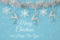 Fondo de la Navidad con la guirnalda festiva del árbol, los ciervos blancos, y los copos de nieve blancos de papel sobre fondo az Fotos de archivo